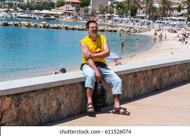 PORT DE SOLLER, SPAIN - JUNE 02, 2016: Tourist on the wall of the beach promenade of Port de Soller in Mallorca, Spain.