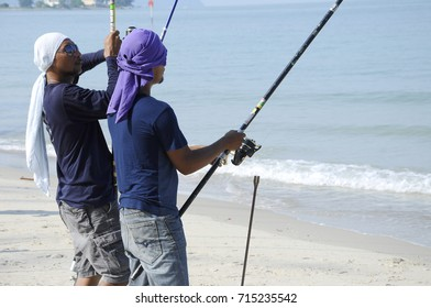PORT DICKSON, MALAYSIA -APRIL 28, 2017: Anglers are fishing on Port Dickson Beach. They use different kinds of fishing rods and bait