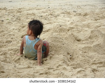 PORT DICKSON, MALAYSIA -FEBRUARY 17, 2018: An unidentified child is playing sand on the beach. They are cranky forming various forms of sand construction.