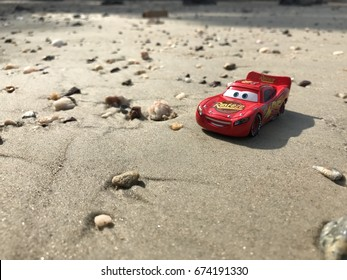 Port Dickson, Malaysia - March 23, 2017: A Lightning McQueen Toy Car at Port Dickson beach. Lightning McQueen is the main character from the popular Disney movie Cars.