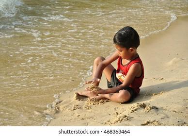 PORT DICKSON, MALAYSIA - MAY 8, 2016: Kids having fun playing sand on the beach.
