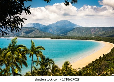 Port Douglas Queensland Australia October 7 2018: Trinity Bay Lookout. Beautiful tropical beach with smoke from bush fire burning in the hills behind. Palm trees, clean beach sand with people swimming