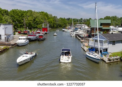 Port Dover, Ontario, Canada - June 19, 2018: Port Dover entrance from Lake Erie, with sailboats, motorboats, commercial ships and harboor installations.