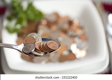PORT ELGIN, ONTARIO - AUGUST 4, 2010: A close up spoonful of Canadian coins symbolizing the cost of living.