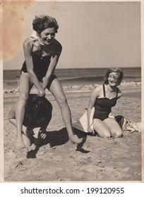 PORT ELIZABETH, SOUTH AFRICA - 1950's: Three young women having the time of their lives on the beach