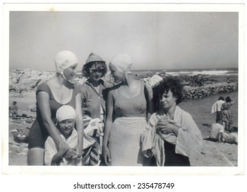 PORT ELIZABETH, SOUTH AFRICA - 1960's: Four young women and a little girl spending time on the beach