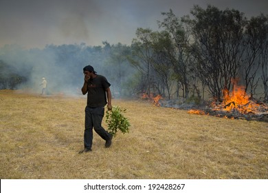 PORT ELIZABETH, SOUTH AFRICA - FEBRUARY 5, 2014 - A man making sure that a wildfire is kept under control that is raging near a home for destitute adults and a children's home.