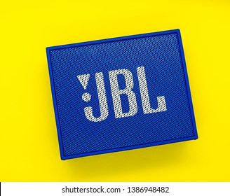 Port Elizabeth, South Africa - May 2, 2019: A photo of a Bluetooth JBL go speaker on a yellow backdrop. The photo is very bright and colorful. The yellow backdrop creates a big contrast in color.