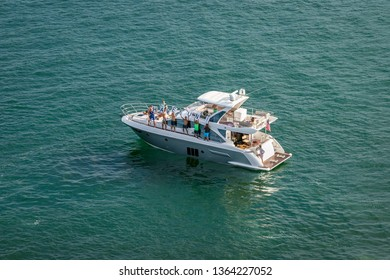 "PORT EVERGLADES, FT. LAUDERDALE - March 17, 2019: Group of people on pleasure boat hold up ""HAVE FUN"" sign and wave to the departing Cruise ships."