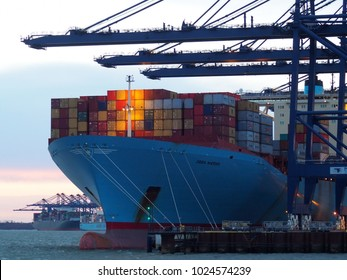 Port of Felixstowe, Suffolk, UK, February 11 2018: Cranes loading containers onto the Ebba Maersk cargo ship at dusk with sunset in background