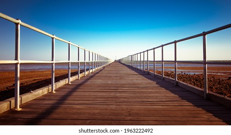 Port Germein Jetty. Longest wooden jetty in South Australia. Built by John Wishart in 1881. Wooden deck with metal rails stretch into the distance as far as the eye can see. Central vanishing point.