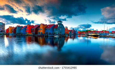 Port in Groningen in the Netherlands. Boats, houses and beautiful sky at sunrise reflected in the sea. There are dramatic clouds in the sky.
