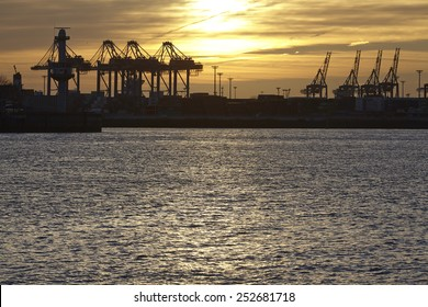 The Port of Hamburg with some container gantry cranes as silhouettes against the sun taken at sunset.