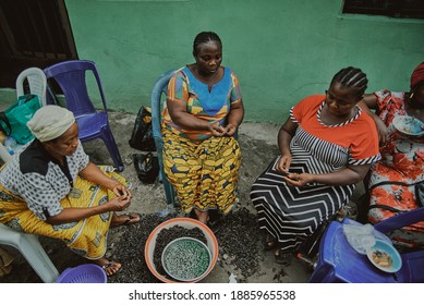 Port Harcourt, Nigeria - November 27, 2020: Women shelling periwinkles in preparation for a meal.