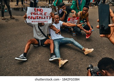 Port Harcourt, Nigeria - October 20, 2020:  A Protester sitting on the floor in Port Harcourt raising placards and signs for the #Endsars protests in Nigeria.