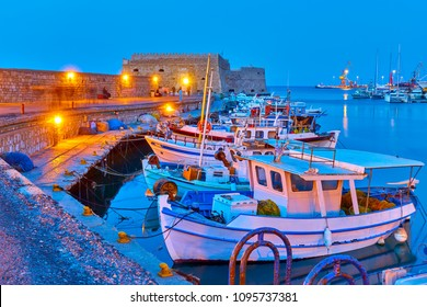 Port of Heraklion with old fishing boats at twilight  Crete, Greece