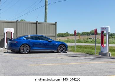 PORT HOPE, CANADA - June 7, 2019: Blue Tesla Model S plugged-in, recharging at Tesla Supercharger.