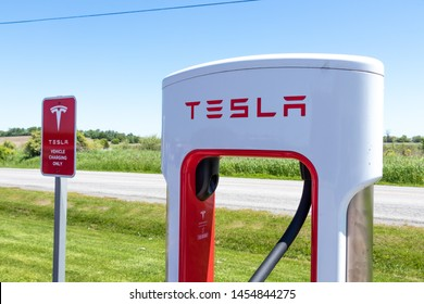 """PORT HOPE, CANADA - June 7, 2019: Top of Tesla Supercharger next to Tesla """"Electric Vehicle Only"""" warning sign."""