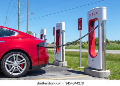 PORT HOPE, CANADA - June 7, 2019:  Metallic Red Tesla Model S plugged-in, charging at Tesla Supercharger Station in Port Hope, Ontario.