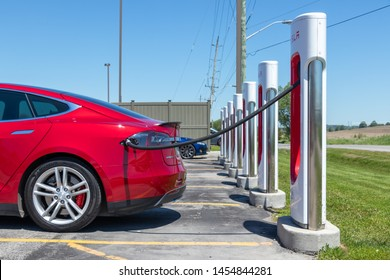 PORT HOPE, CANADA - June 7, 2019: Metallic Red Tesla Model S plugged-in, charging at Tesla Supercharger Station.
