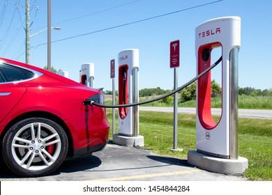 PORT HOPE, CANADA - June 7, 2019: Red Tesla Model S parked, recharging at Tesla Supercharger Station.