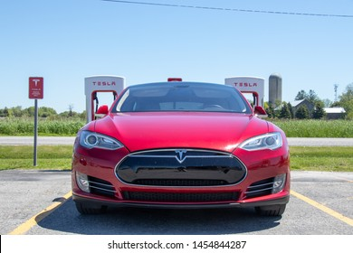 PORT HOPE, CANADA - June 7, 2019: Front-view of Red Tesla Model S while vehicle parked at Tesla Supercharging Station.