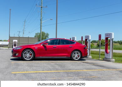 PORT HOPE, CANADA - June 7, 2019: Tesla Model S parked at Tesla Supercharger Station, plugged-in and charging.
