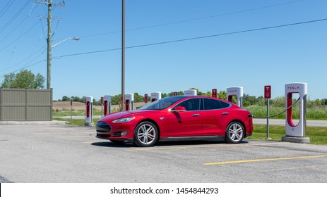 PORT HOPE, CANADA - June 7, 2019: Red Tesla Model S plugged-in and charging at Tesla Supercharger Station, in Port Hope, Ontario.