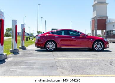 PORT HOPE, CANADA - June 7, 2019: Red Tesla Model S parked at Tesla Supercharger Station, recharging.