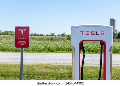 """PORT HOPE, CANADA - June 7, 2019: Top of Tesla Supercharger next to Tesla """"Electric Vehicle Only"""" warning sign with rural farm in background."""