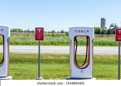 """PORT HOPE, CANADA - June 7, 2019: Tesla Supercharger and Tesla """"Electric Vehicle Only"""" warning sign with rural farm in background."""