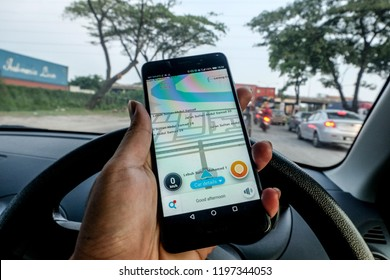 """Port Klang, Malaysia - Circa October, 2018: A man holding the phone with Waze navigation app inside the car. Waze has gain popularity for its good navigation. """