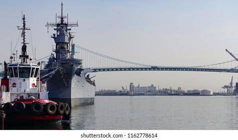 Port of Los Angeles main channel with a tugboat moored in front of the Battleship Iowa, the Vincent Thomas suspension bridge behind them
