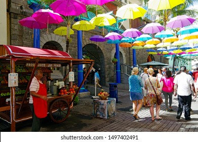 PORT LOUIS/ MAURITIUS - AUGUST 16, 2018: People walking across the main alley of Caudan Waterfront in Mauritius. The city is the country's economic, cultural, political center and most populous city.