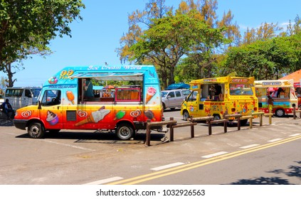 PORT LOUIS / MAURITIUS - FEBRUARY 24, 2018: Several ice-creamers with his traditional cars - mobile sweetshops waiting for first tourists on tropical beach. Hot day on Mauritius Island.