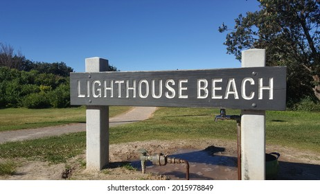 Port Macquarie, Australia - Jul 2021: View of the wooden sign of Lighthouse Beach at the access path to the sandy beach, blue sky background. It is located below Tacking Point Lighthouse