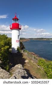 Port Manec'h Lighthouse against blue sky.