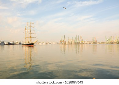 Port. Marine boat. sailer, lighthouse, port cranes, ships. Arrival of the sailboat to the port.