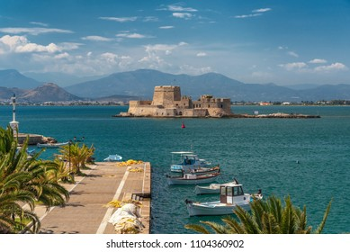 The port of Nafplio city in Greece with small boats and Bourtzi castle at the background.