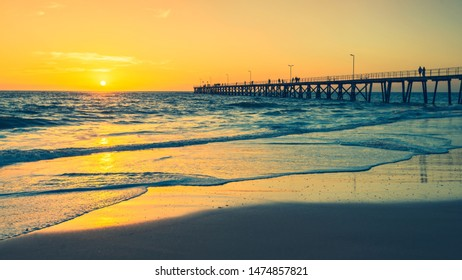 Port Noarlunga Jetty with walking people at sunset viewed from the beach side, South Australia
