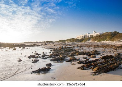 PORT NOLLOTH, SOUTH AFRICA - SEPTEMBER 20th, 2016: Coastal properties in Port Nolloth, South Africa. Sunset with blue sky, light clowds, rocks, ocean and sand dunes.