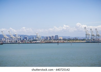 Port of Oakland cranes, Oakland downtown in the background, San Francisco bay area, California