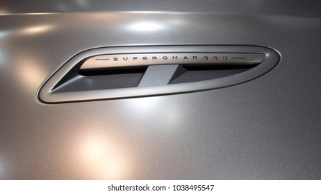 Port on a hood of a silver sports car with the word supercharged.