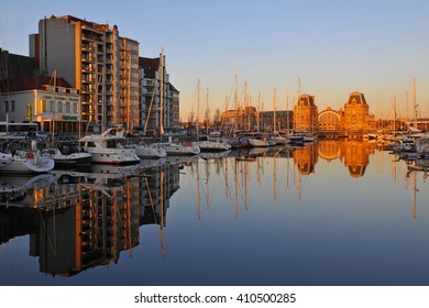 "The port of Oostende at sunset and its train station bathed in sunlight, Belgium. Translation left: ""Chinees restaurant"" = Chinese restaurant."