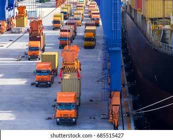 Port operation loading container onboard.The trucks is queuing for loading containers to the vessel by port crane.