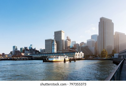 The Port of San Francisco at sunset with a boats near it. Panorama view to the city skyline from the bay at the evening