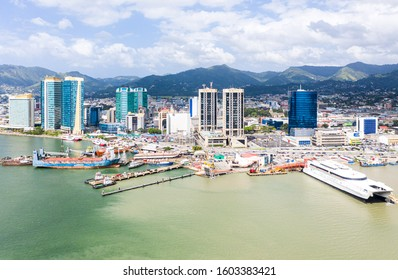 Port of Spain, Trinidad and Tobago - Dec 24 2019: Aerial view of the capital city of a tropical island. Skyscrapers of the downtown and a busy sea port with commercial docks and passenger ships.