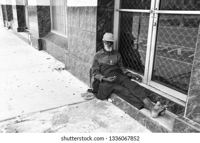 Port of spain, Trinidad and Tobago - November 28, 2015: old bearded man african American hobo or homeless sitting at building window in street outdoor barefoot as poverty symbol