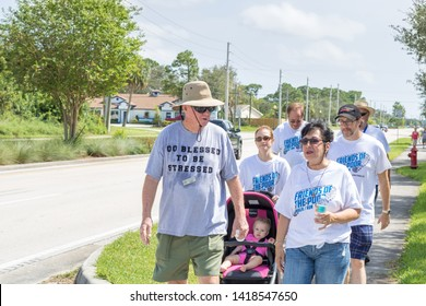 Port St. Lucie, Florida; USA; Sept. 30, 2017.  A mom and her baby join this Charity walk event. The catholic church community of St Vincent de Paul holds a charity aimed to bring awareness