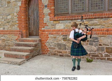 Port Stanley, Falkland Islands - November 20, 2017: A little boy playing pipes wearing a typical kilt.